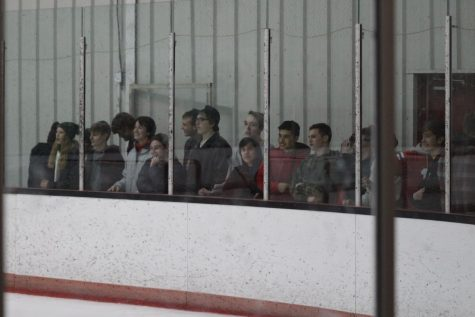 Students line up at the glass to encourage the hockey team as they win 3-0