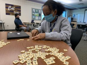 After completing her work in Mr. Nelson's Compass class, Eyerusalem practices spelling English words using letter chips.