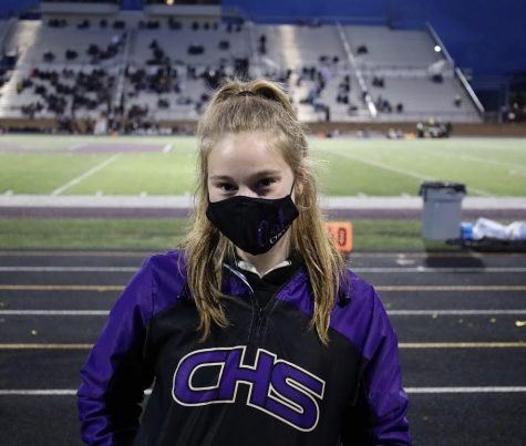 At the Grandville v. Caledonia football game, Morgan Baisch bundles up in her jacket as temperatures begin to drop.