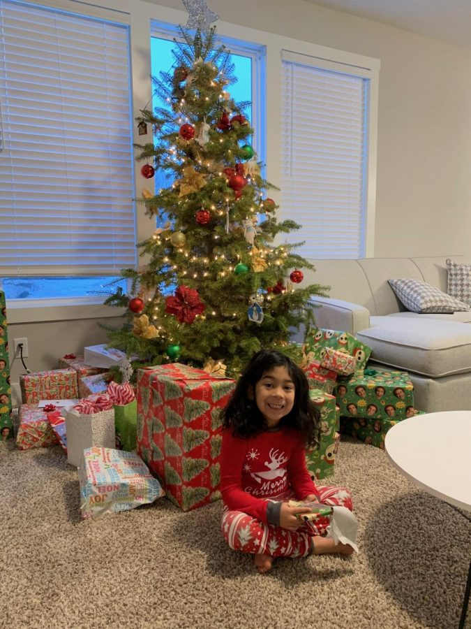 A child opens the first present on Christmas morning.