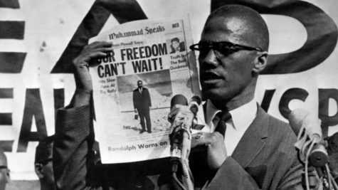 "Malcolm X shows a news article titled ""Our freedom can't wait!"""