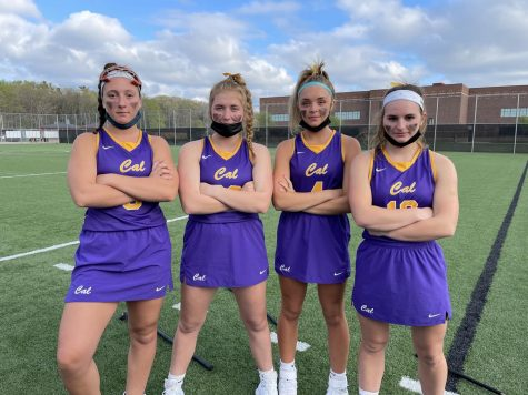 Defenders Reagan Weiss, Brinlee Barry, Addison Deveny, and Audrey Kord pose up before a game against Spring Lake.