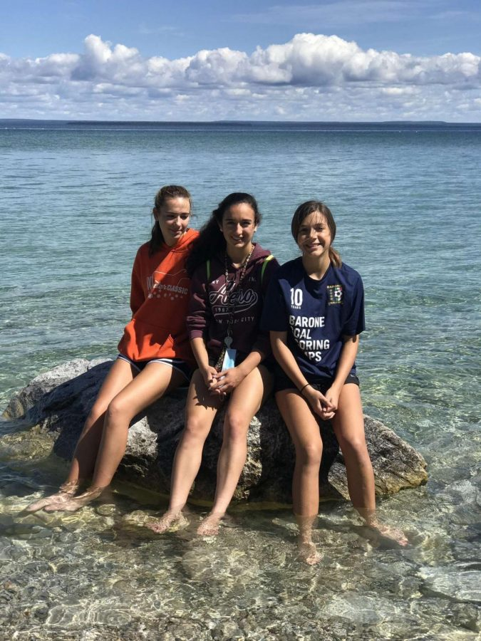 Juniors Veronica Foster-Toledano, Mia Stiver, and Alivia LoGiudice take a refreshing break by dipping their feet in Lake Michigan on a sunny day.