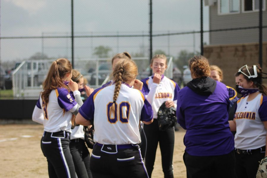 Girls on the Caledonia JV softball team socially distance and pull up their masks while they huddle together after an inning against Rockford.