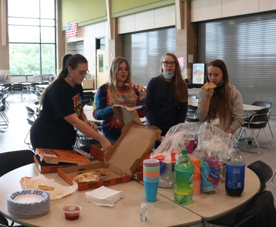 Attendees to the first Key Club meeting eat pizza and socialize.